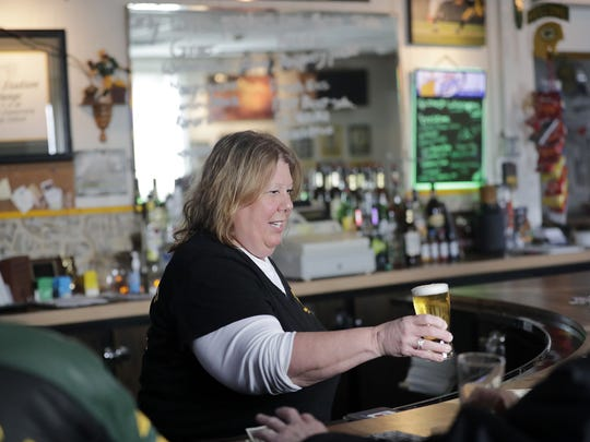 "Bartender Susan Fuller serves a beer at The Packer Stadium Lounge on Wednesday afternoon. She's worked at the bar for 16 years. ""It's like a family to me,"" she said."