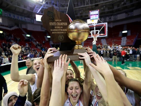 Appleton North's Sydney Levy, center, raises the championship trophy with teammates after defeating Mukwonago during the Division 1 state championship game March 10, 2018, at the Resch Center in Ashwaubenon.