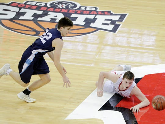 Roncalli's Mitchel Schneider chases after the ball after Marathon's Carter Hanke tripped during Saturday's WIAA Division 4 boys basketball state championship game at the Kohl Center in Madison.