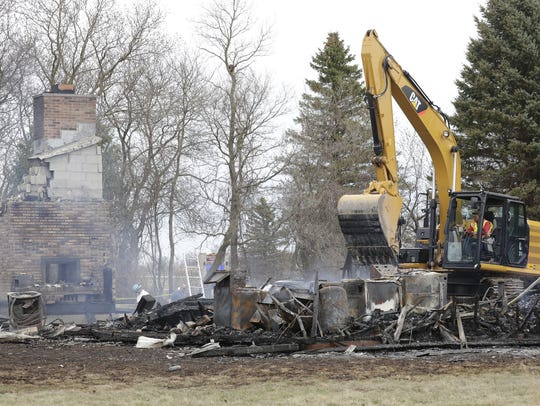 Smoldering rubble is cleared from the scene of a fire at 3302 Breezewood Lane in Clayton on Tuesday. The remains of two people were found inside the home.