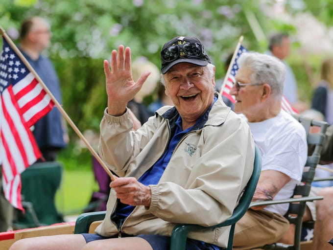 A member of the Kiwanis Club waves to parade goers