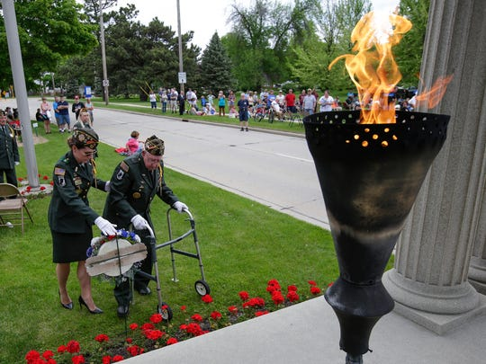 FILE - VFW honor guard Julie Rozum, left, and color guard captain Harold Kummer place a commemorative wreath in front of the Soldiers and Sailors Monument as the Eternal Flame burns in remembrance of those who served during the Memorial Day ceremony in 2018.