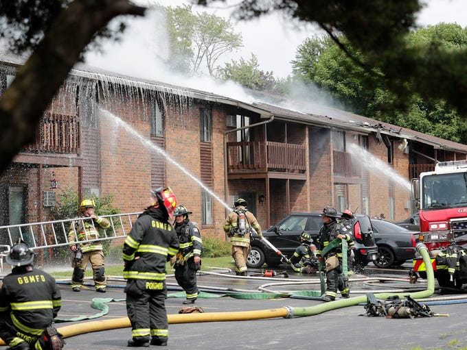 Firefighters work at the scene of an apartment building
