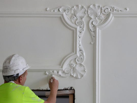 A worker paints the Crystal Ballroom walls at the Hotel