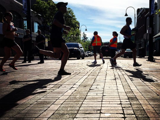 Runners are silhouetted by the sun as they cross Bank Street during the 29th People's United Bank Vermont City Marathon on Sunday morning.