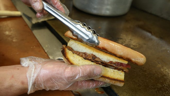 Cook Chase Mastro puts hotdog on a bed of bacon as he creates a Boston Terrier Dog as he works the lunch hour at Dog Town.