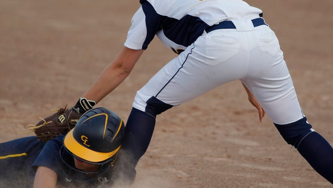Grand Ledge's Kaylee Dumond, left, is safe at third base against Haslett's Bayelee Hodge (15) Tuesday, May 16, 2017, at Ranney Park in Lansing, Mich.