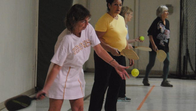 Faith Brown of Chincoteague, far left, reaches back for an underhand serve during a pickleball game inside the Chincoteague Island Activity Center Saturday, Jan. 9, 2016. The indoor pickleball league on Chincoteague is free and open to anyone over the age of 18.