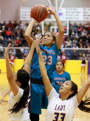 Shiprock's Tanisha Begay shoots over a pair of Kirtland Central defenders on Feb. 15 at Bronco Arena in Kirtland.