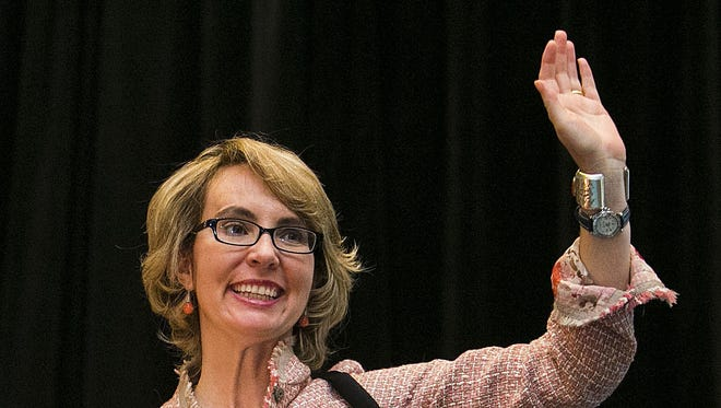 Former U.S. Rep. Gabrielle Giffords greets the audience at the 101st Arizona Town Hall meeting Tuesday at Talking Stick Resort near Scottsdale. Giffords was awarded the organization?s Shirley Agnos Legacy Award. Gifford?s husband, Mark Kelly, also is a recipient of the award but was not present.  Tom Tingle/The Republic 112811sm-PNI1128-met giffords award- 11-27-2012-Former Rep. Gabrielle Giffords, cq, greets the crowd at the 101st Arizona Town Hall meeting at the Talking Stick Resort in Scottsdale, Tuesday, 11-27-2012.  Giffords was awarded the Arizona Town Hall Shirley Agnos Legacy Award, (foreground).  Her husband, Mark Kelly, was also a recipient of the award but was not present.    Photo by Tom Tingle/The Arizona Republic