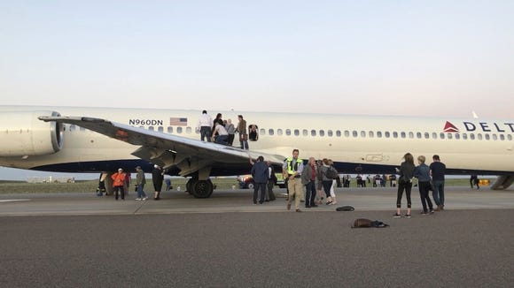 Passengers exit a plane and stand on the tarmac of