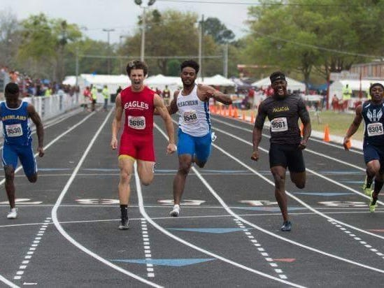Pine Forest's Marcus Reaves celebrates crossing the finish line in first place during the running of the 100-meter dash recently.