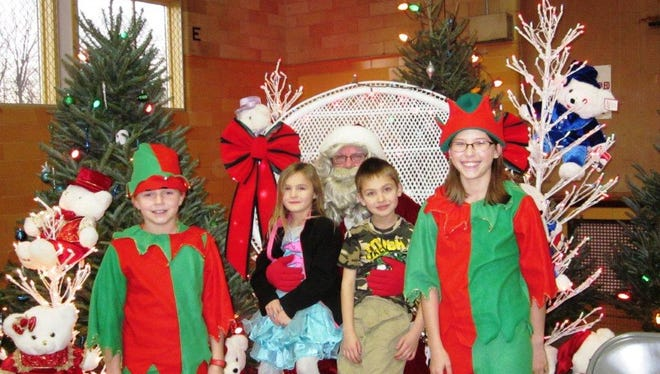 Tabitha, left, and Sydney Lemens served as  Santa's elves while Waylon and Meredith DeVillers visited with Santa.