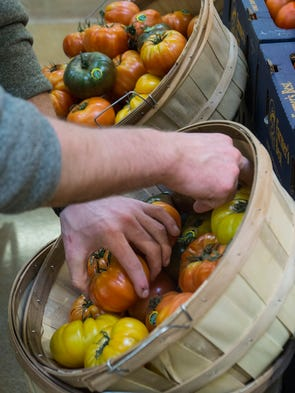 Heirloom tomatoes fill baskets.