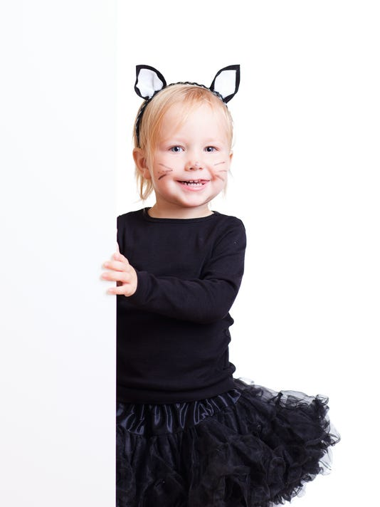 Girl in black cat costume with banner