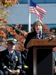 Knoxville Mayor Madeline Rogero, right, speaks in front of a flag flying at half-staff during a memorial service held at the Firefighters Memorial Park in downtown Knoxville on Wednesday, Oct. 12, 2016. Family and friends gathered to remember the retired KFD firefighters who have passed away since the last memorial service.