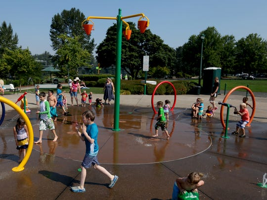 Children play at the splash pad fountain at Riverfront Park in Salem on Wednesday, Aug. 2, 2017. Temperatures are expected to reach 110 degrees on Wednesday.