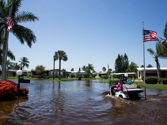 A woman drives through the flooded streets of the Citrus Park community in Bonita Springs on Tuesday, August 29, 2017.