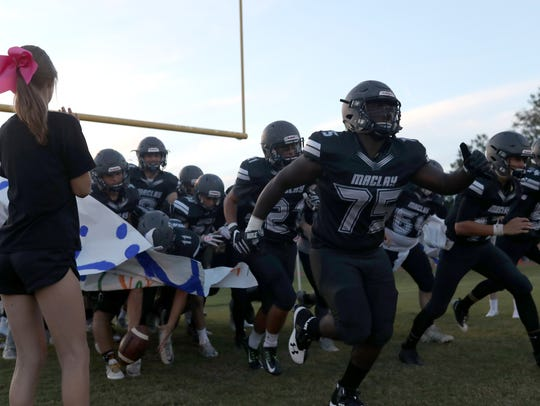 Maclay's players run out on to the field for their
