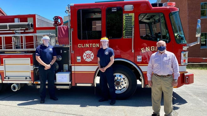 The Clinton Fire Department received FFR-MW face shields. Showing off the masks are Clinton firefighters Alan Lutes (left) and Thomas Fazio with Harvard engineer Bob Vinci, who started the effort.
