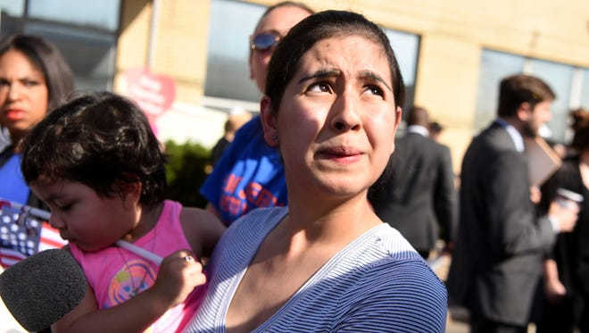 Over five hundred people attend a Father's Day Rally for Family Unity organized by immigration rights advocates outside of the Elizabeth Detention Center in protest of ICE tearing families apart and forcing children and parents to separate at the border. Sharon Chajon holds her daughter Rachel 2, of Somerset, during the rally. Chajon's husband a citizen of Guatemala was picked up by ICE ten months ago outside of their home. Sharon and her children are United States citizens. Sunday, June 17, 2018.
