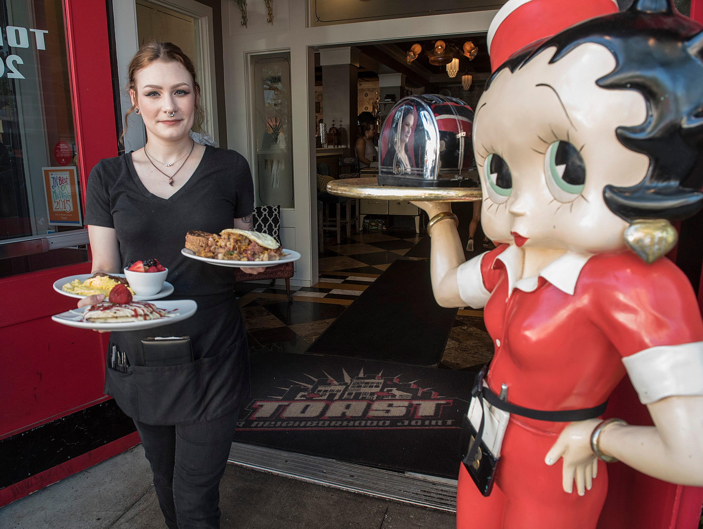 Courtney McManus brings an order to patrons at Toast,