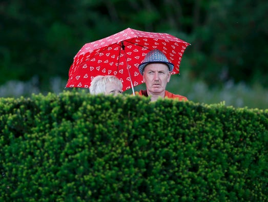 Spectators carry an umbrella as it rains at the Wimbledon Tennis Championships on Day 6.