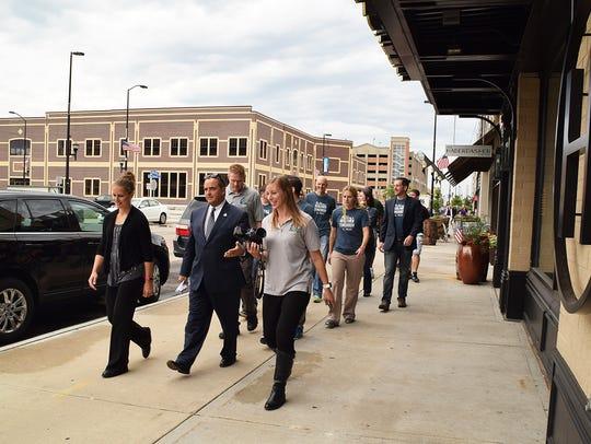 Mayor Jim Schmitt leads organizers on a walk in downtown