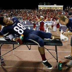 Tempe High athletic trainer Crystal Fix helps Alex Gomez stretch before a high-school football game against Tempe McClintock last week. Advocates say that having licensed athletic trainers on hand helps to minimize life-threatening or long-term consequences from injuries suffered at a developmental age.