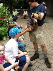 In this June 15, 2015 photo, zookeeper Ian Shelley lets elementary students at Ewell School pet a snake. Students from the offshore Smith Island school got the VIP treatment at the Salisbury Zoo. Students were randomly picked for a special day at the zoological park, where they petted animals, toured displays and had a picnic lunch.