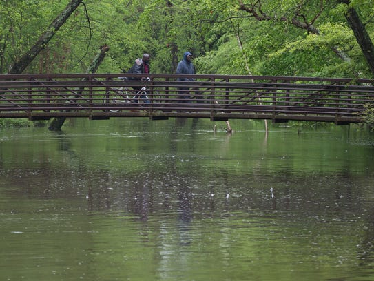 Two men cross over a water way at Silver Lake Park
