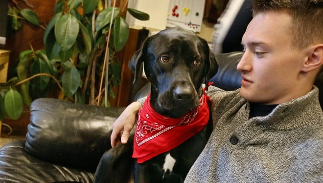 Air Force veteran Austen Koczent, 23, of Geneva, visits with Hans, a black lab mix that came from a kill shelter as a puppy, at the Veterans Outreach Center's Richards House in Rochester.