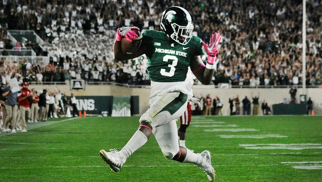 Michigan State's LJ Scott runs into the end zone untouched to put Michigan State up 17-9 after the extra point late in the fourth quarter of the victory over the Indiana Hoosiers at Spartan Stadium in East Lansing, Michigan, on October 21, 2017.