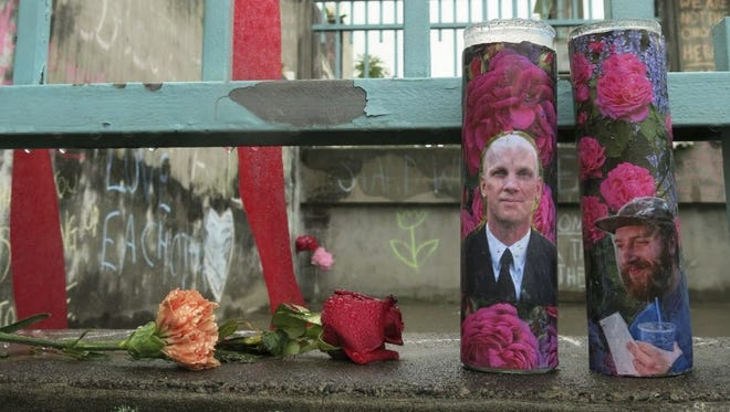 Candles memorializing Rick Best, left, and Taliesin Myrddin Namkai-Meche.