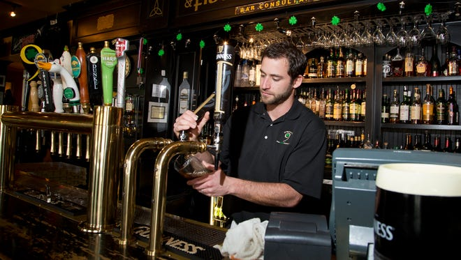 Bartender/Manager Jason Mugg pours a beer for a customer at O'Bryan's Nine Irish Brothers in West Lafayette.