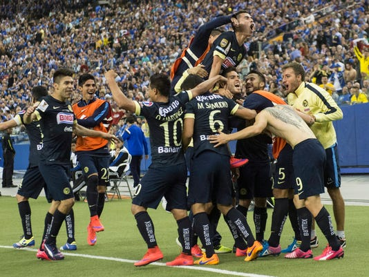 Members of Club America gather around teammate Dario Benedetto (9) to celebrate his second goal against the Montreal Impact during second half of the CONCACAF final Wednesday, April 29, 2015, in Montreal. (Paul Chiasson/The Canadian Press via AP) MANDATORY CREDIT