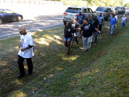 L'Sana D'Jahspora leads a group down a path he describes as his son's last steps on North Parkway, Friday afternoon as a part of the National Stolen Lives Family Tour. D'Jahspora's son Cinque was shot by a Jackson police officer in 2014.
