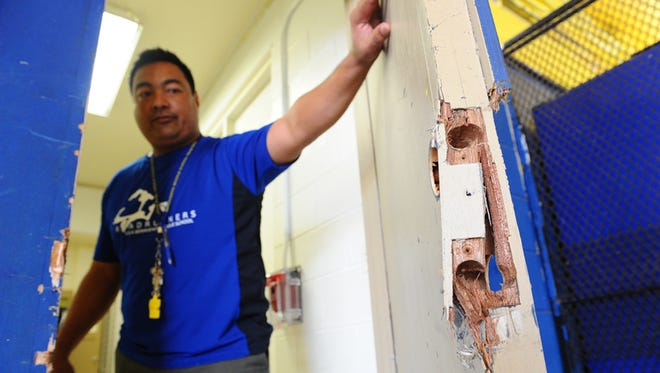 Assistant Principal Kin Perez shows damage to a school office door at V.S.A. Benavente Middle School yesterday morning (CQ Feb. 26), after burglars struck the Dededo school overnight. Masako Watanabe/Pacific Daily News/mwatanabe@guampdn.com