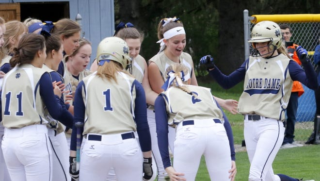 Notre Dame players celebrate after Courteney Crater, far right, homered in the first inning Tuesday in a 5-4 victory over Thomas A. Edison in Southport.