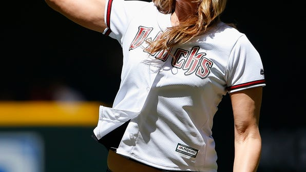 FILE - In this April 12, 2015, file photo, gold medalist Jennie Finch throws out a ceremonial first pitch prior to a baseball game between the Arizona Diamondbacks and the Los Angeles Dodgers, in Phoenix. Finch is pitching youth softball this spring as an ambassador for Major League Baseball. The commissioner's office announced Wednesday, Jan. 25, 2017, that she'll join Cal Ripken Jr. and Ken Griffey Jr. as MLB youth ambassadors. (AP Photo/Ross D. Franklin, File)
