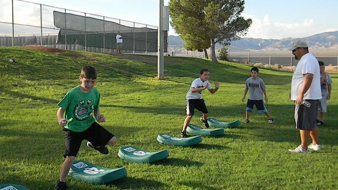Nick Montoya, associate director of the Mesquite Athletics and Leisure Services Department, runs youth through conditioning exercises during the 2012 Youth Football Camp.