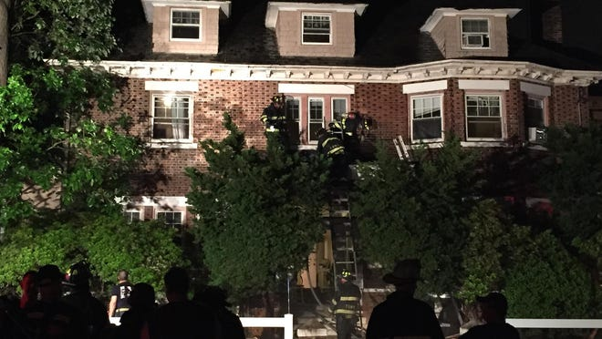 Flames climbed up the exterior of a three-story home on Wednesday night before being knocked down under a steady rain, officials said.