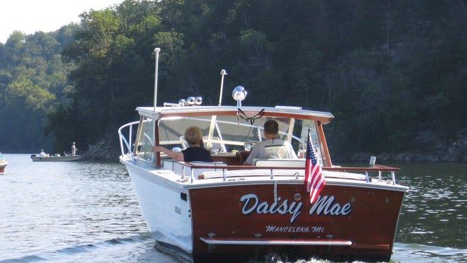 A classic wooden cruiser follows the shoreline.