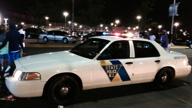 An abandoned State Police cruiser sits in the MetLife Stadium parking during a disturbance at Hot 97 Summer Jam