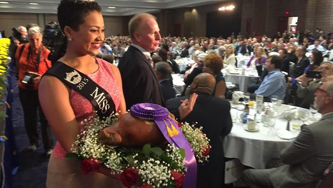 Miss Kentucky shows off the champion ham during the charity auction.