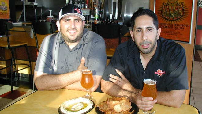 Kareem Dada, left, Chafic Dada enjoy a craft beer alongside pita chips and hummus at one of the two Pita Kabob restaurants the brothers own in Visalia.