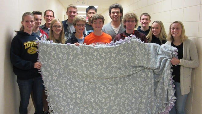 The St. Mary Catholic High School cross country team made a fleece blanket and donated it to Fox Valley Hematology and Oncology in solidarity with the soccer team, after hearing about the fundraiser-game that the soccer team played for the Fight Back Foundation. Photo courtesy of St. Mary Catholic Schools