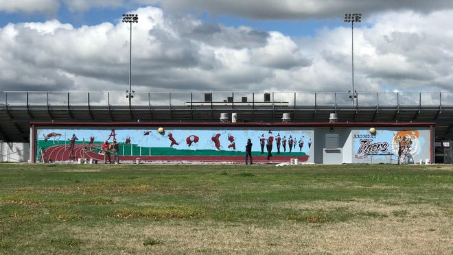 Artist work on Noble Stadium's new mural.