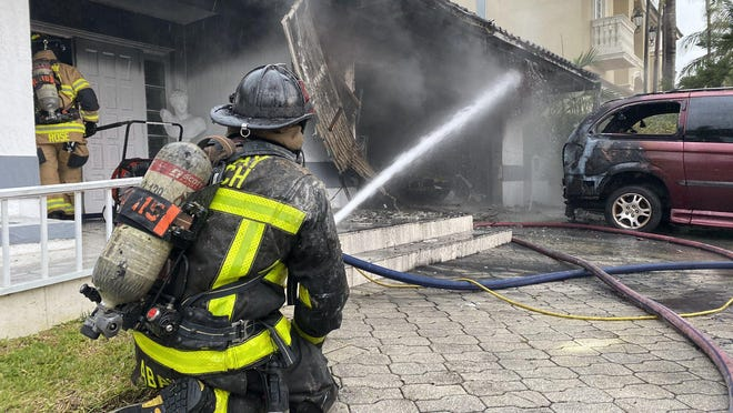 A Delray Beach firefighter extinguishes a fire at a home on Gardenia Drive on Thursday, June 18, 2020.