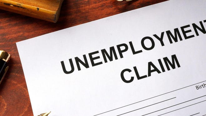 Unemployment claim document on table with open pen resting on it